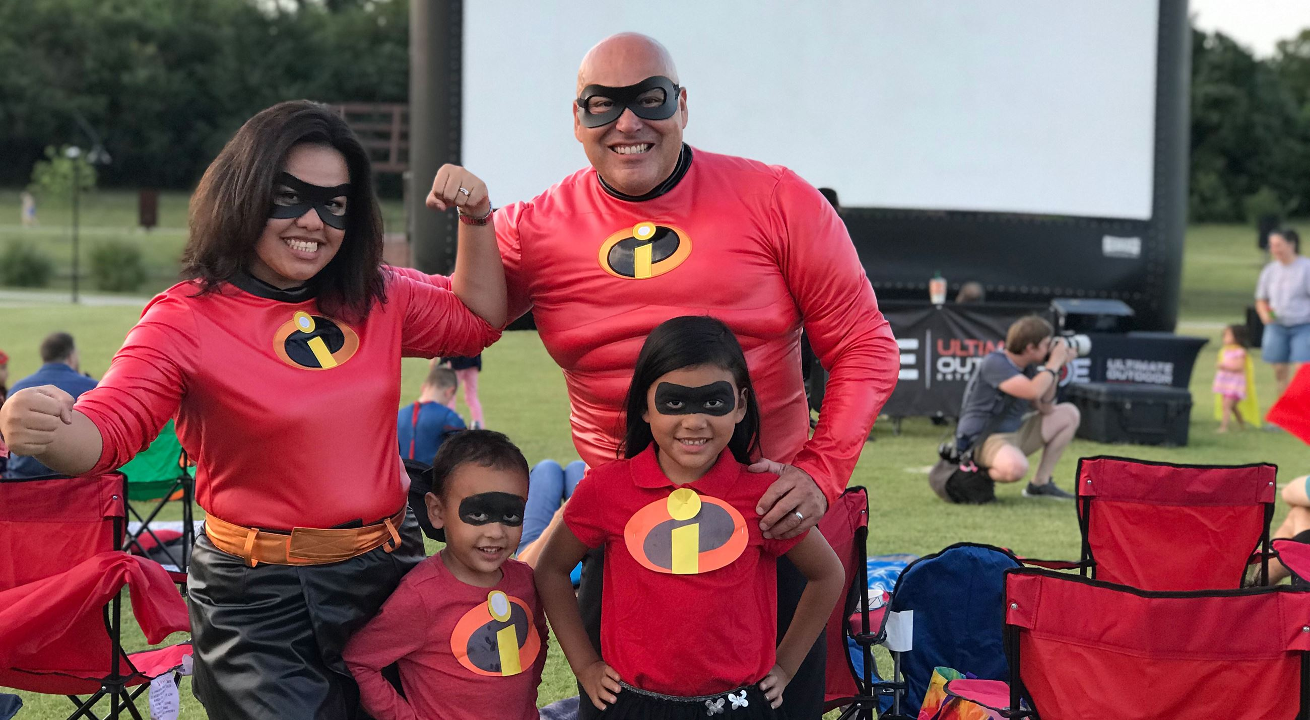 Family dressed as superheroes in the park