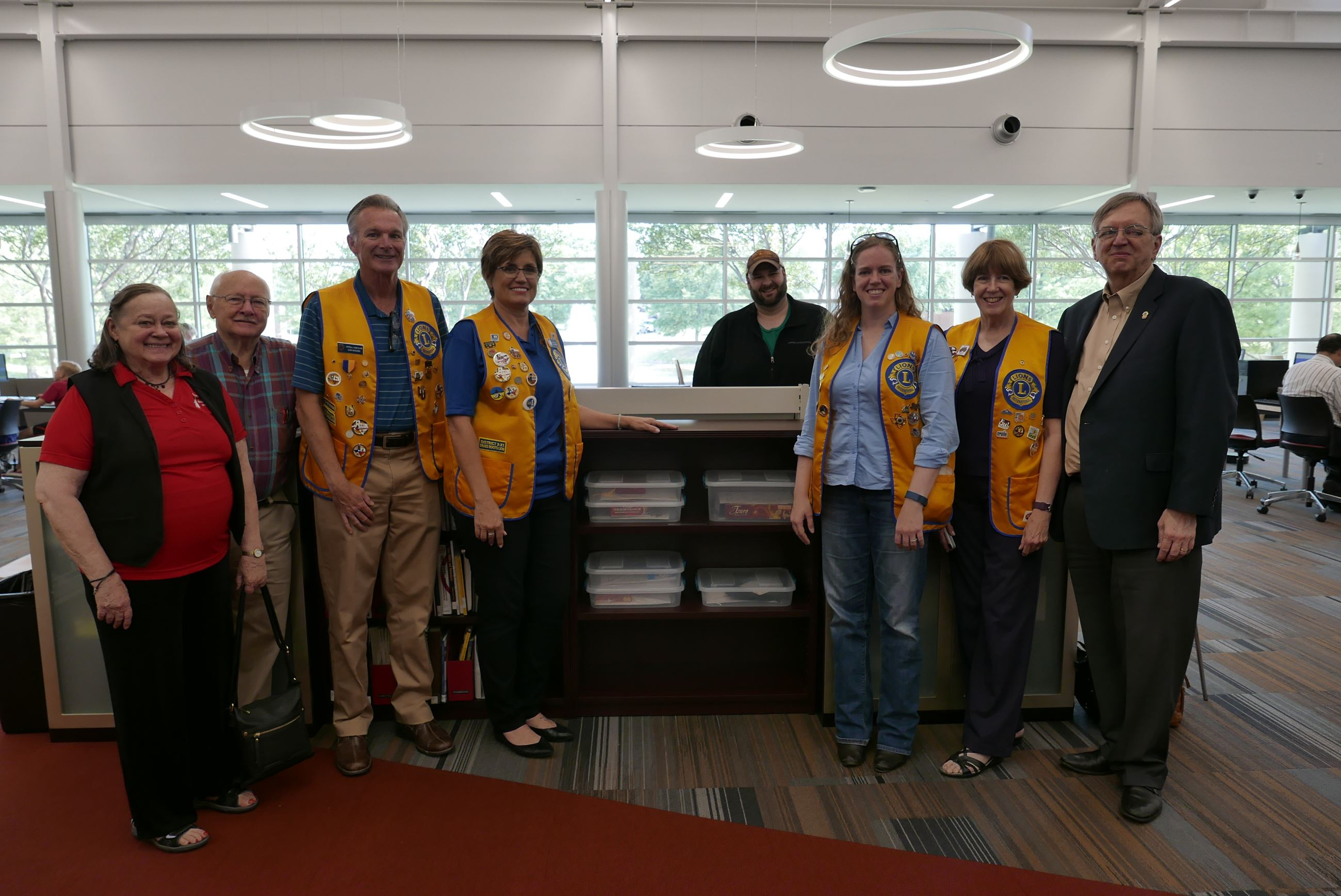Members of the Coppell Lions Club standing next to the Braille Games Shelf.