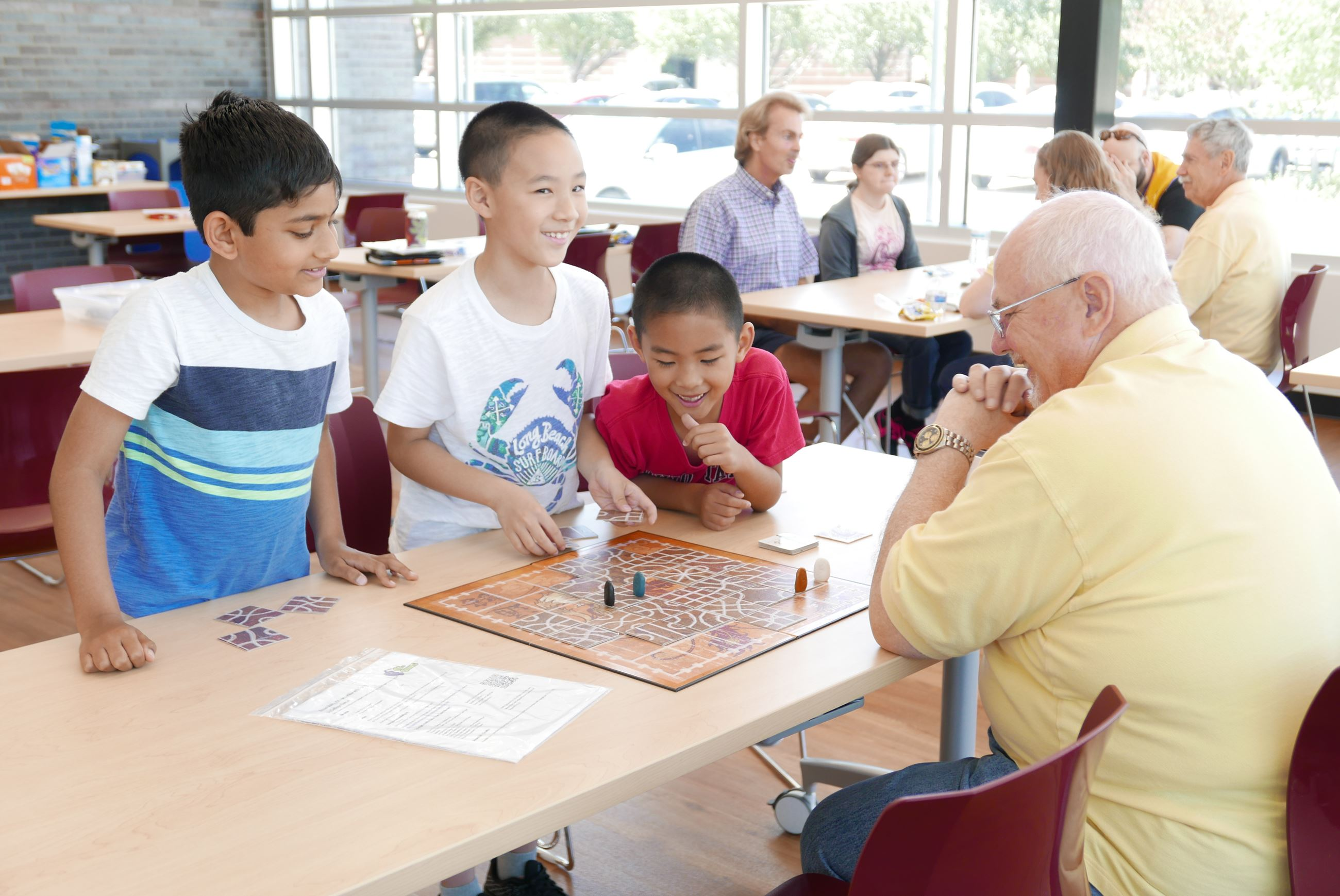 Coppell Lions Club members and children playing board games.