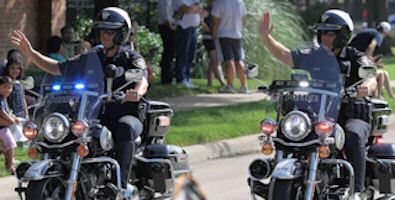Two Officers on Motorcycles Waving